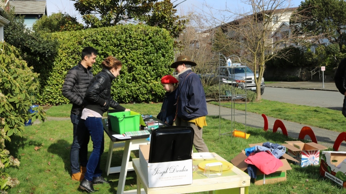 Selling ordinary items alongside participant-made objects at the yard-sale-of-the-future event in a residential neighborhood.