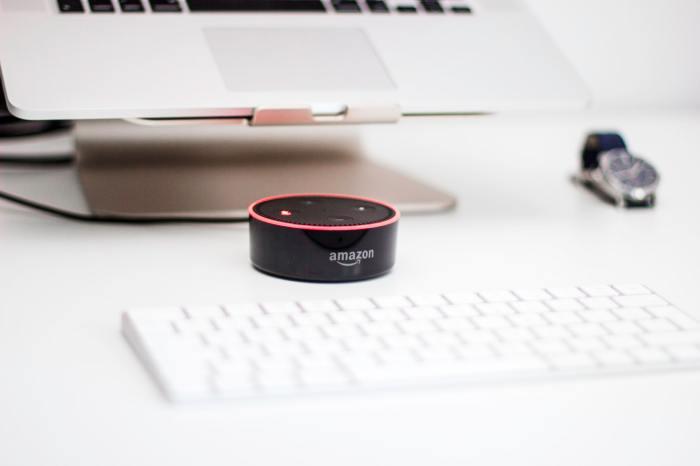 Amazon Echo Dot by a laptop and keyboard